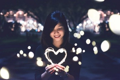 A girl holding a light heart at night